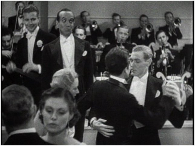 "That's Dick Powell and Al Jolson smiling at the dancing male couple in the 1934 movie ""Wonder Bar"""